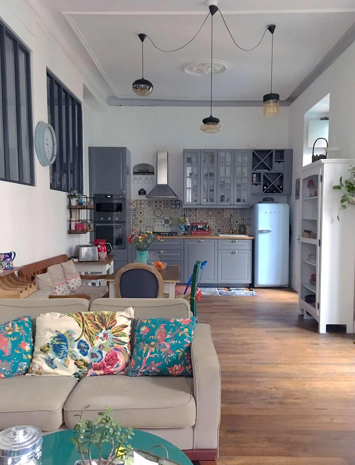 Photo de la pièce de vie avec dans le fond la cuisine , murs blancs et parquet chêne doré